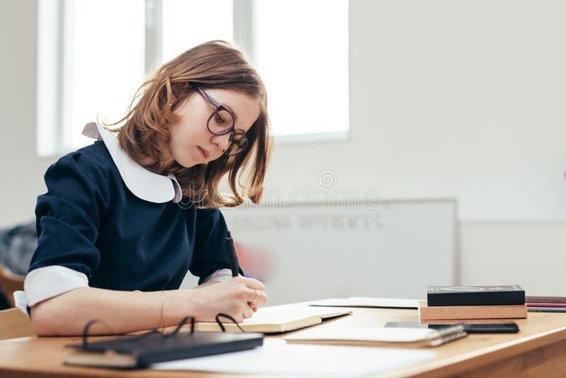 Estudante que senta-se na educação da lição da escola da sala de aula, aprendendo, estudando fotografia de stock