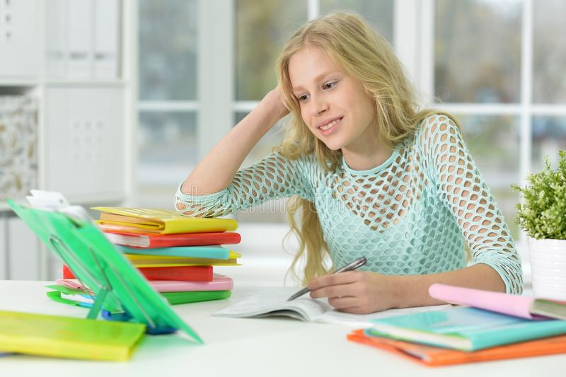 Estudante que senta-se na mesa e que estuda em casa foto de stock royalty free