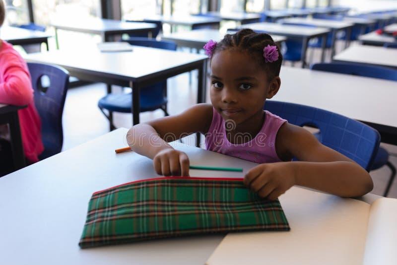 Estudante que senta-se na mesa e que olha a câmera na sala de aula foto de stock royalty free