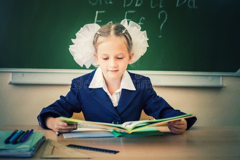 Estudante que senta-se na mesa, na sala de aula da escola, e no livro de leitura fotos de stock