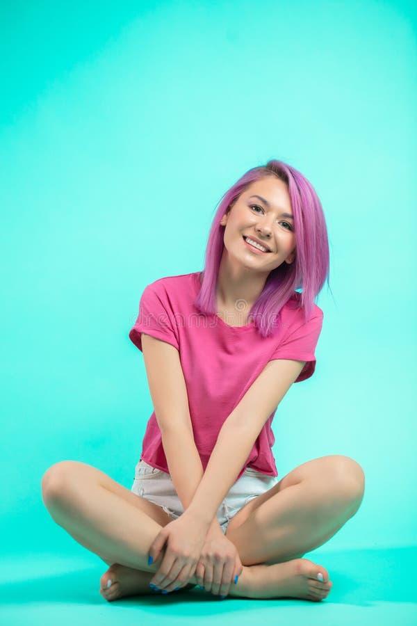 Estudante que senta-se no estúdio Moça com o cabelo cor-de-rosa reto que senta-se no assoalho foto de stock royalty free