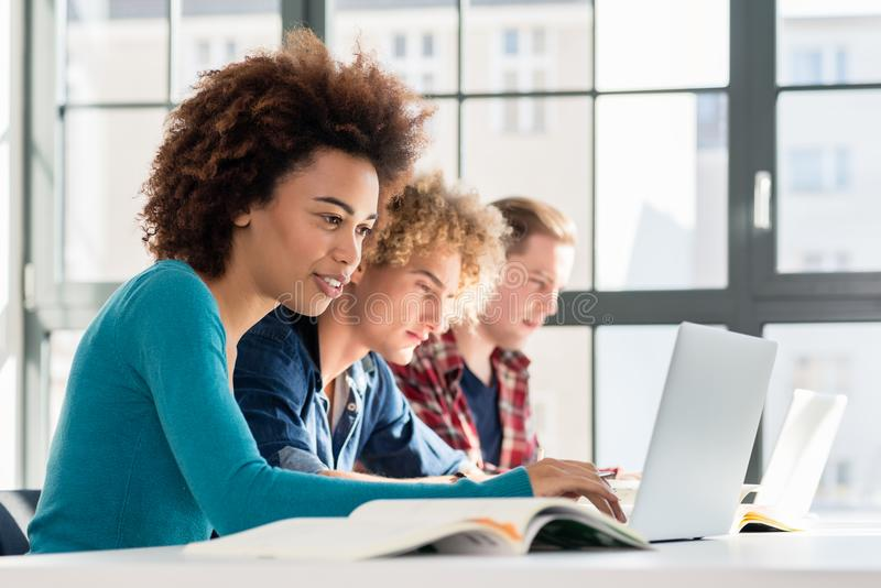 Estudante que sorri ao usar um portátil para a informações online ou o v imagem de stock