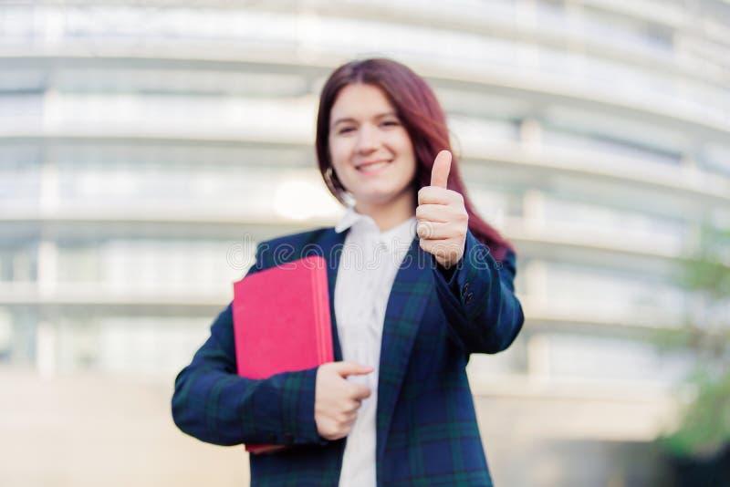 Estudante que sorri com o polegar acima do gesto fotografia de stock