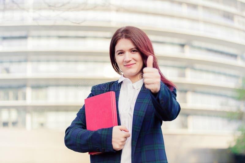 Estudante que sorri com o polegar acima do gesto foto de stock royalty free