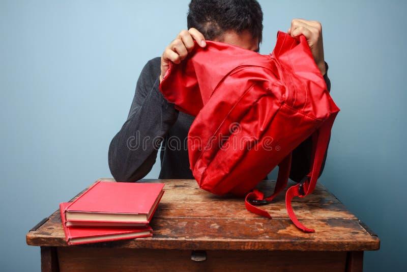 Estudante que tenta encontrar algo em seu saco foto de stock royalty free