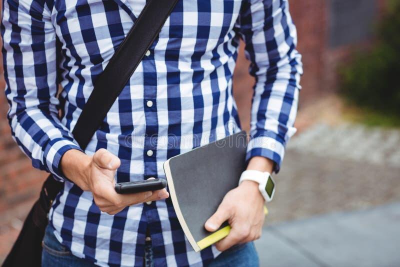 Estudante que usa o telefone celular no terreno fotos de stock