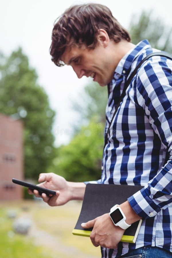 Estudante que usa o telefone celular no terreno imagens de stock royalty free
