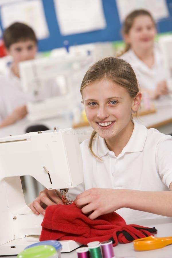 Estudante que usa uma máquina de costura na classe sewing imagens de stock