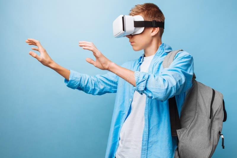Estudante que veste vidros da realidade virtual, em um fundo azul imagens de stock