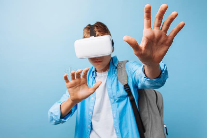 Estudante que veste vidros da realidade virtual, em um fundo azul imagem de stock royalty free
