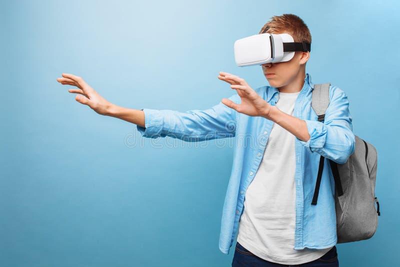 Estudante que veste vidros da realidade virtual, em um fundo azul foto de stock