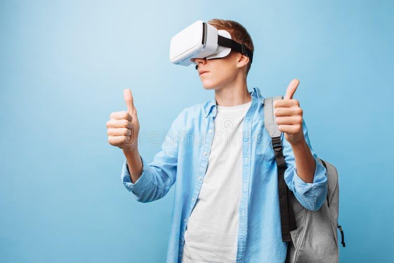 Estudante que veste vidros da realidade virtual, em um fundo azul fotos de stock