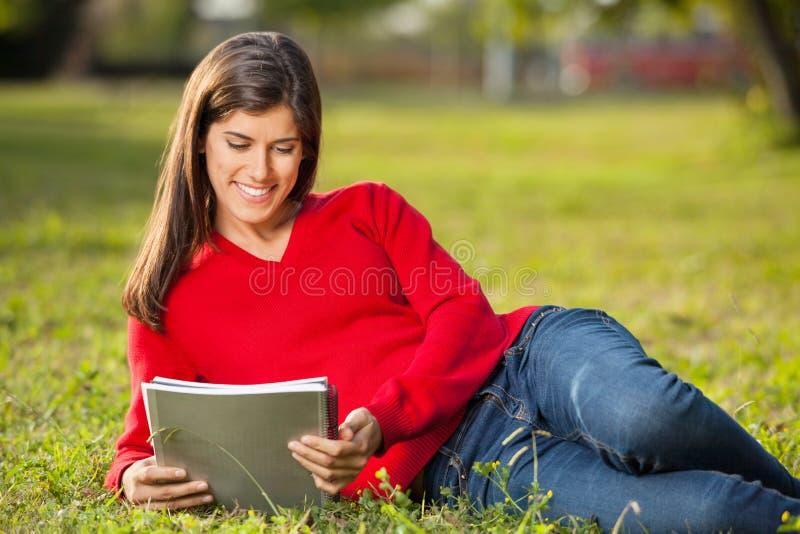 Estudante Reading Book While que relaxa na faculdade imagens de stock royalty free