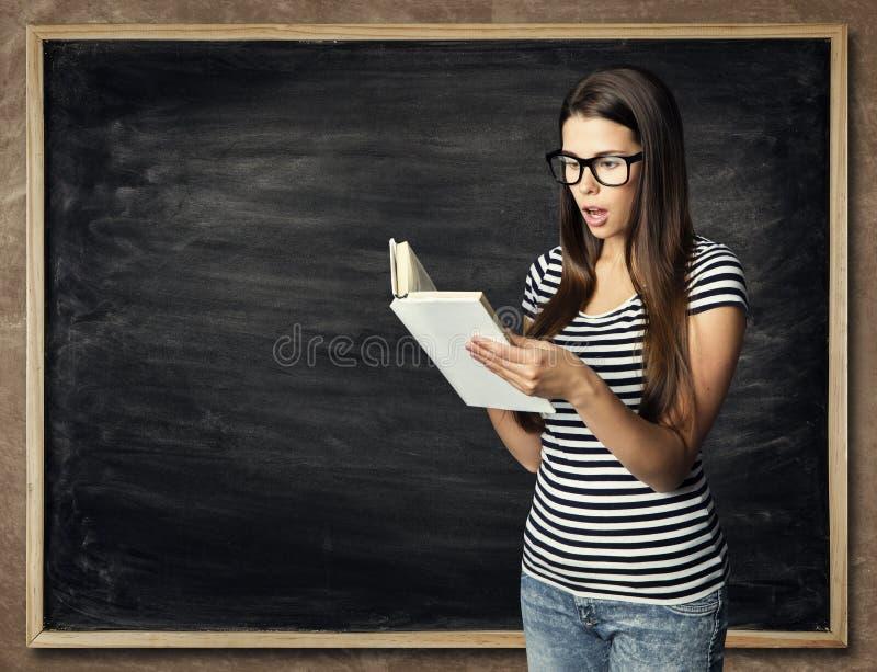 Estudante Reading Book sobre o fundo do quadro-negro, mulher surpreendida imagens de stock
