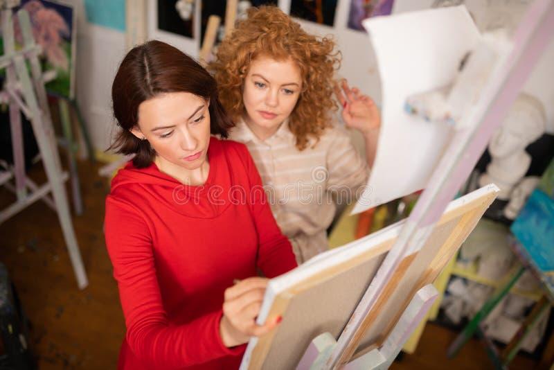 Estudante ruivo encaracolado que olha seu desenho do professor de arte fotografia de stock royalty free