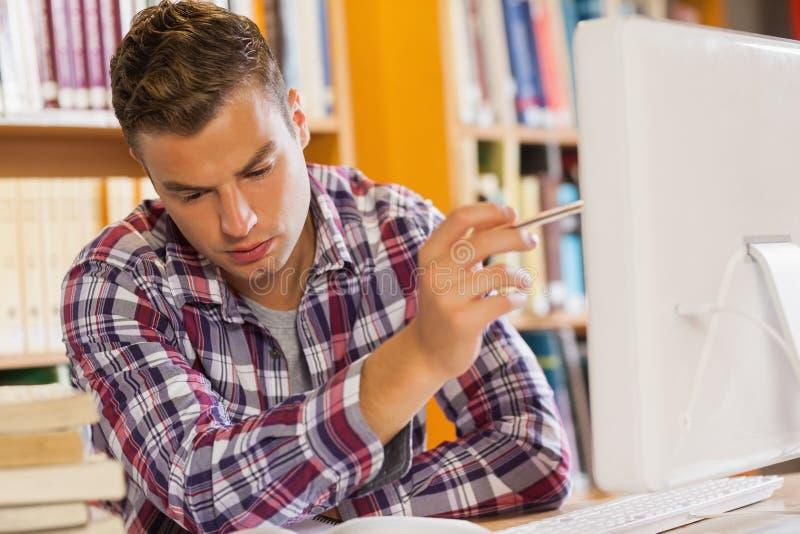 Estudante sério considerável que aponta no computador fotografia de stock