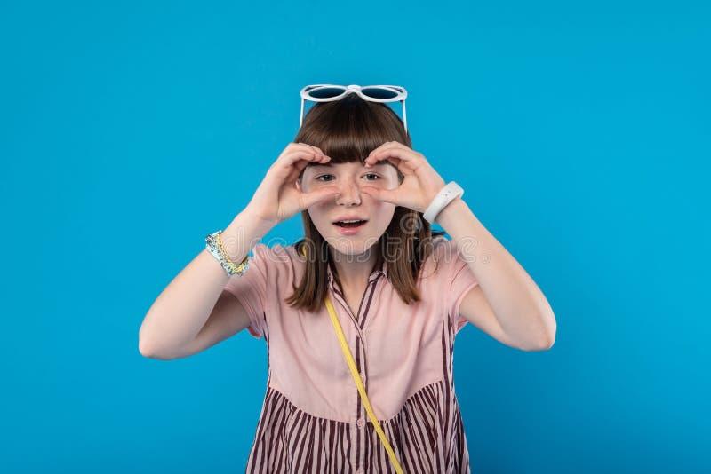 Estudante satisfeita que guarda binocular imaginário imagens de stock