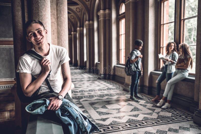 Estudante seguro e bem sucedido Estudante masculino considerável que senta-se nos trilhos e que olha a câmera foto de stock
