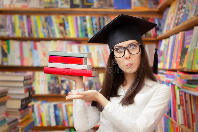Estudante surpreendido com o tampão da graduação que guarda livros fotografia de stock royalty free
