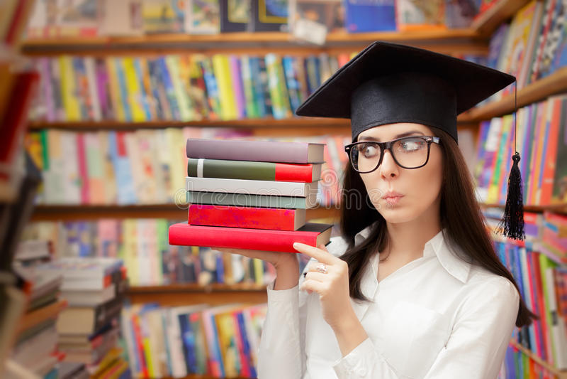 Estudante surpreendido com o tampão da graduação que guarda livros imagens de stock royalty free