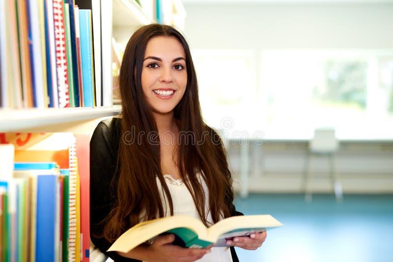 Estudante trabalhador positivo que guarda um livro aberto foto de stock royalty free