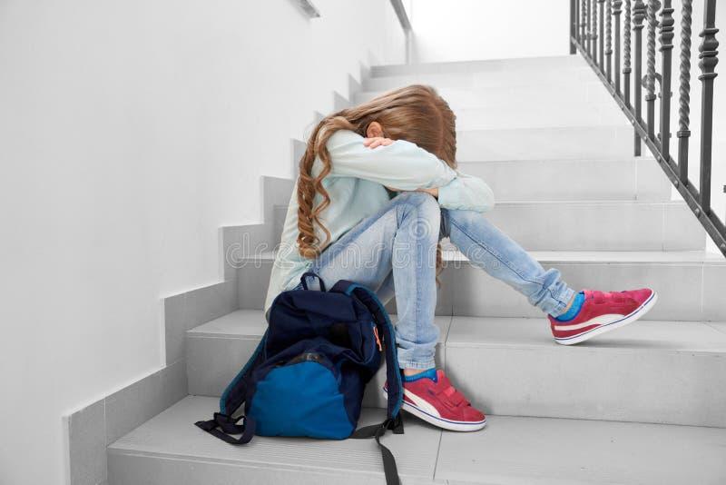 Estudante triste que senta-se no v?o das escadas, cara escondendo fotografia de stock royalty free