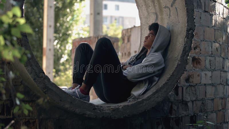 Estudante triste solitário em capuz sentado sozinho em prédio abandonado, isolamento de puberdade fotografia de stock