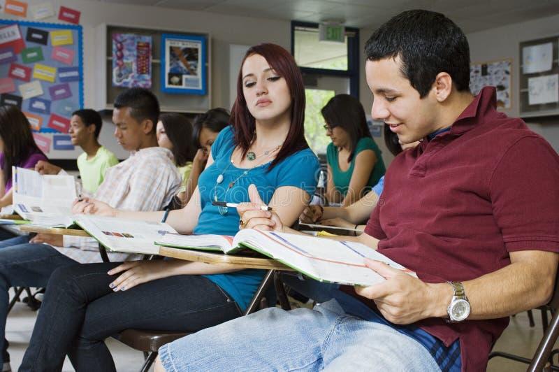 Estudante Trying da High School para ler as respostas do vizinho fotos de stock royalty free