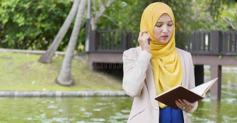 A estudante universitário bonita aprecia ler e pensar no parque imagens de stock royalty free