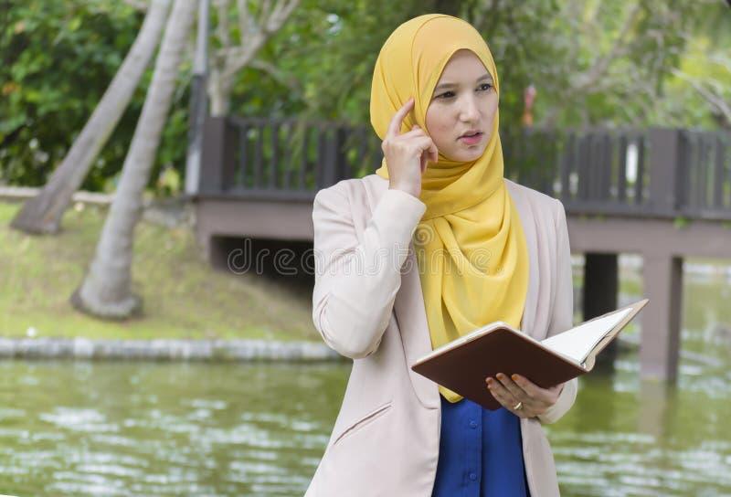 A estudante universitário bonita aprecia ler e pensar no parque fotografia de stock royalty free