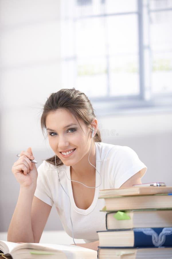 Estudante universitário bonito que aprende em casa o sorriso fotografia de stock royalty free