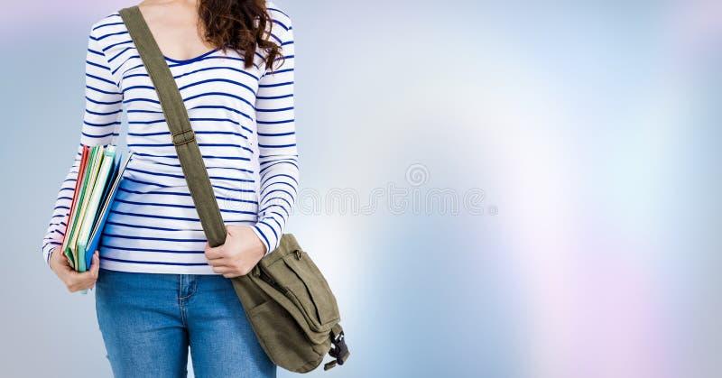 Estudante universitário com livros e saco contra o fundo abstrato roxo fotos de stock