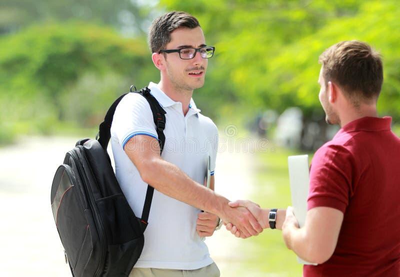 A estudante universitário com vidros encontra seu amigo no parque da faculdade e imagens de stock royalty free