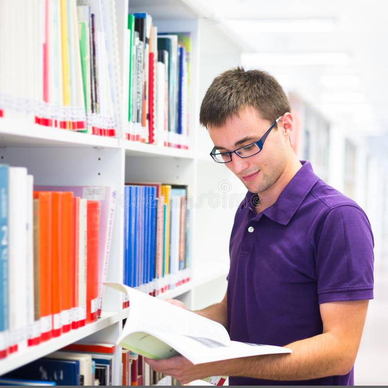 Estudante universitário considerável na biblioteca imagens de stock