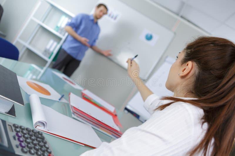 Estudante universitário consideravelmente fêmea dos jovens que senta-se na sala de aula foto de stock
