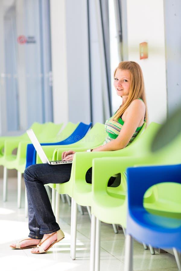 Estudante universitário consideravelmente fêmea que trabalha em seu laptop imagem de stock
