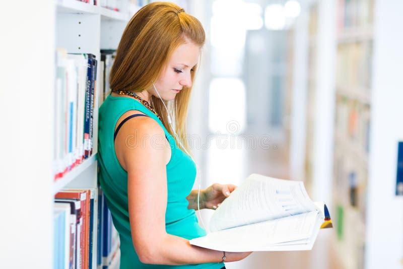 Estudante universitário consideravelmente novo em uma biblioteca imagens de stock royalty free
