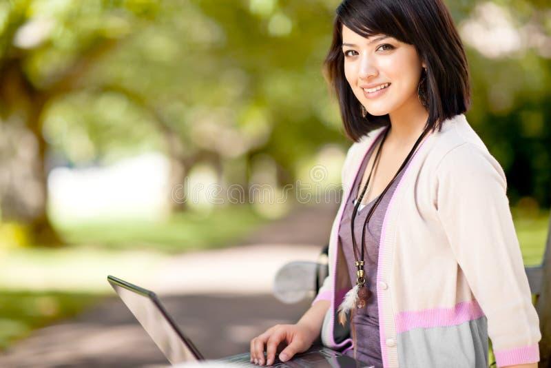 Estudante universitário da raça misturada com portátil foto de stock