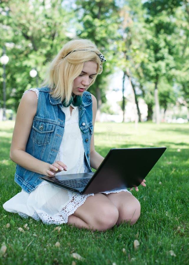 Estudante universitário da raça misturada que senta-se na grama que trabalha no portátil foto de stock