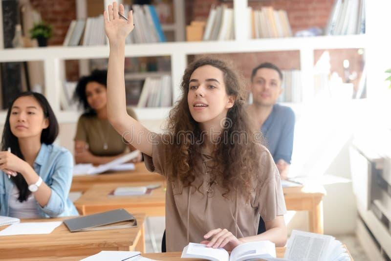 Estudante universitário fêmea adolescente da faculdade que levanta a mão durante a classe foto de stock royalty free