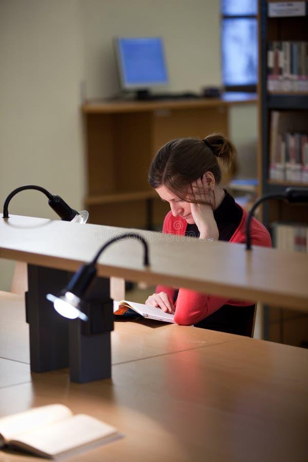 Estudante universitário fêmea bonito em uma biblioteca imagem de stock