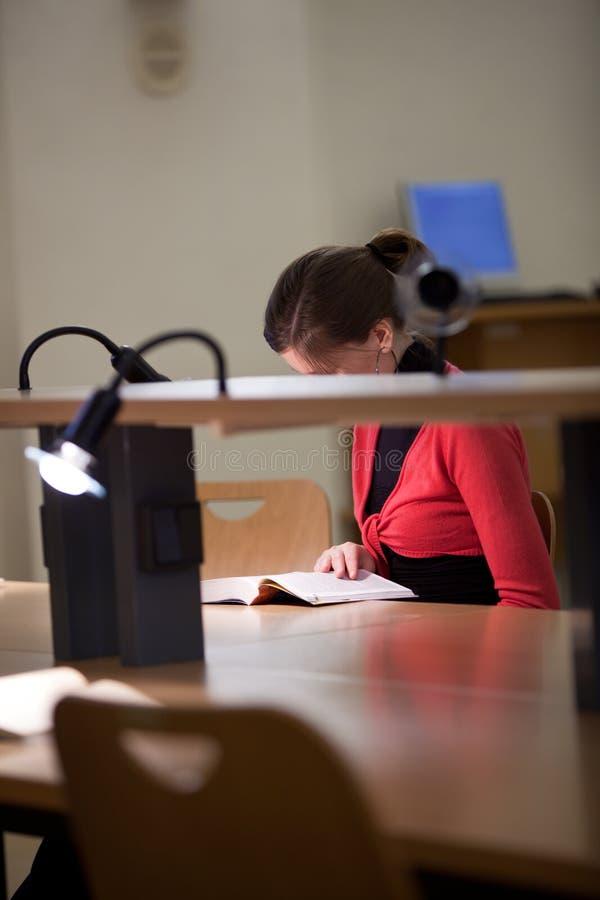 Estudante universitário fêmea bonito em uma biblioteca fotos de stock royalty free