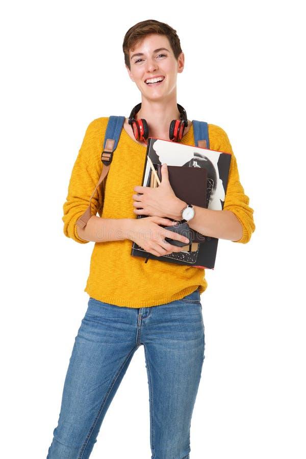 Estudante universitário fêmea de sorriso com saco e livros contra o fundo branco isolado fotos de stock