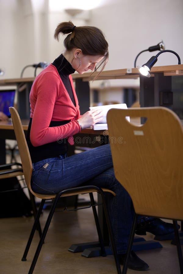 Estudante universitário fêmea em uma biblioteca fotografia de stock