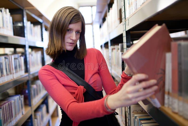 Estudante universitário fêmea em uma biblioteca fotos de stock