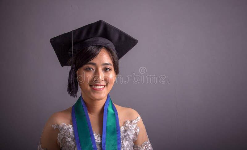 Estudante universitário fêmea no retrato do close up do chapéu da graduação sobre o cinza fotografia de stock