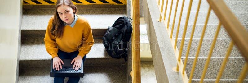 Estudante universitário fêmea nova que senta-se em escadas na escola, escrevendo o ensaio em seu portátil e olhando acima na câme foto de stock