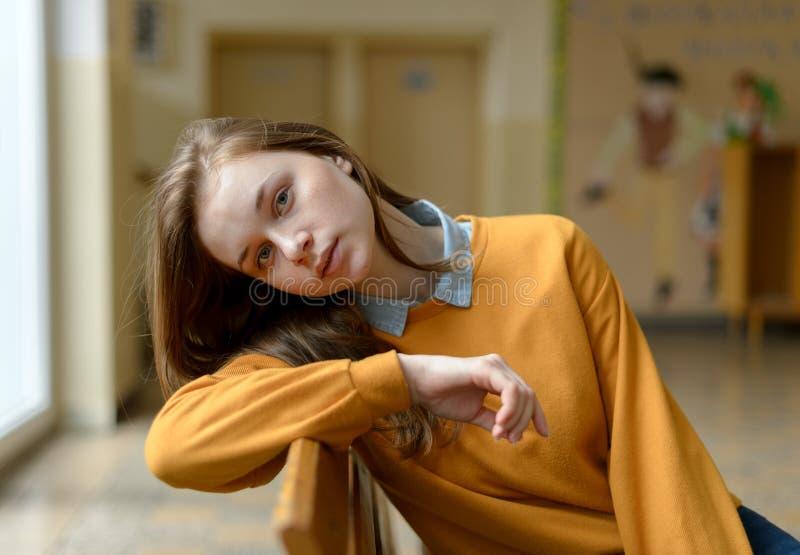 Estudante universitário fêmea só deprimida nova que senta-se em um banco em sua escola, olhando a câmera Tiranizar, depressão imagens de stock