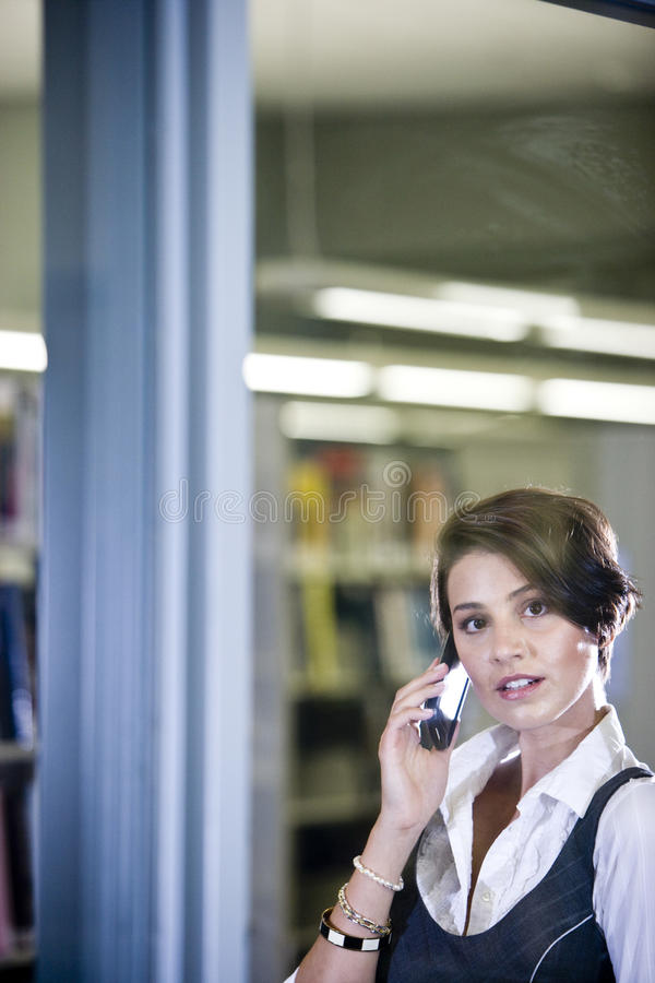 Estudante universitário fora da biblioteca usando o telefone móvel imagem de stock royalty free