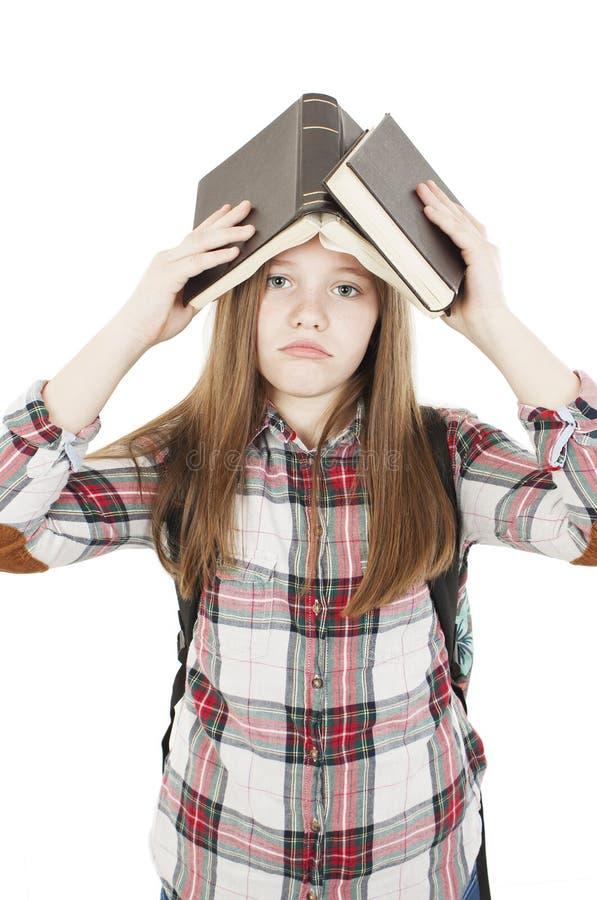 Estudante universitário furada, frustrada e oprimida Moça com uma trouxa em seus livros guardando traseiros sobre sua cabeça imagem de stock